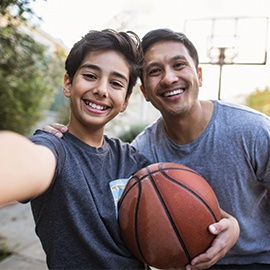 Hispanic-father-and-son-taking-a-selfie-outdoors-whilst-playing-basketball-1130685992_6016x4016